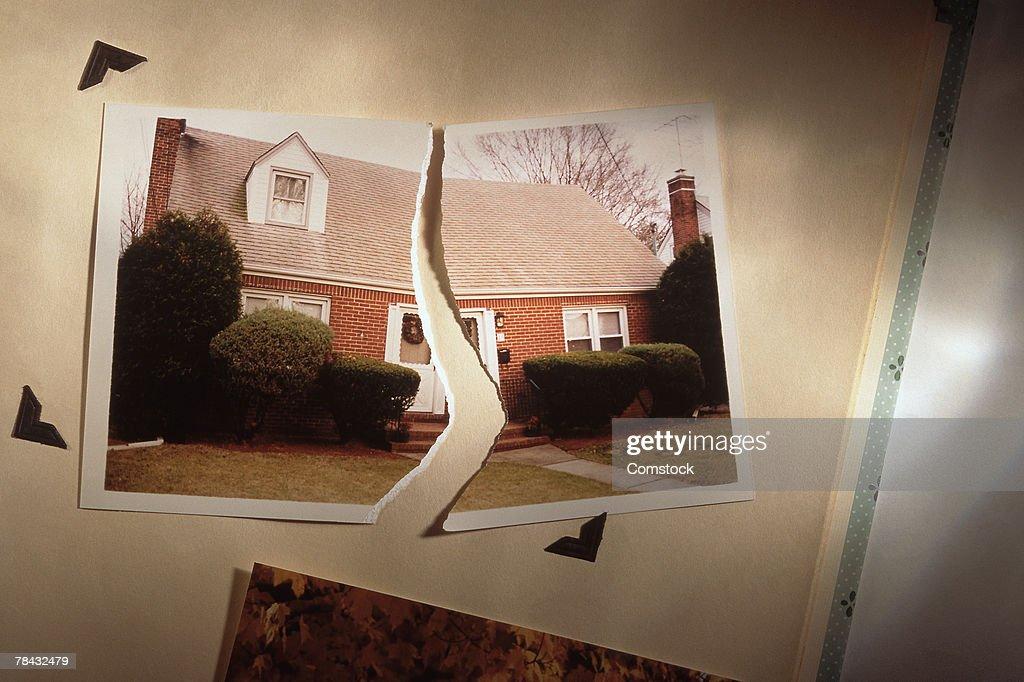Torn photo of home symbolizes divorce : Stock Photo