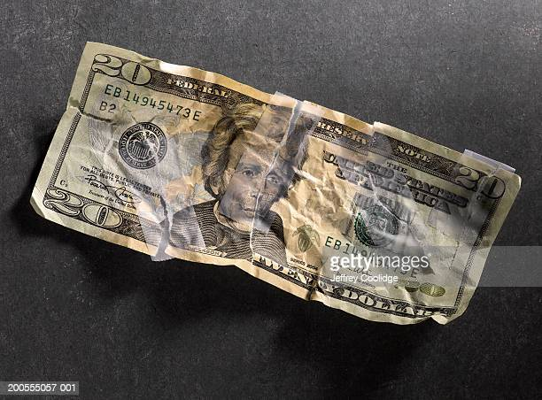 Torn twenty dollar bill, repaired with tape, overhead view