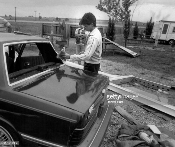 Tornado 168th and Washington St Denvernorth campground shot of John valentine cleaning the broken glass off his car they were shatter when a huge...