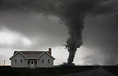 Tornado approaching house in rural landscape