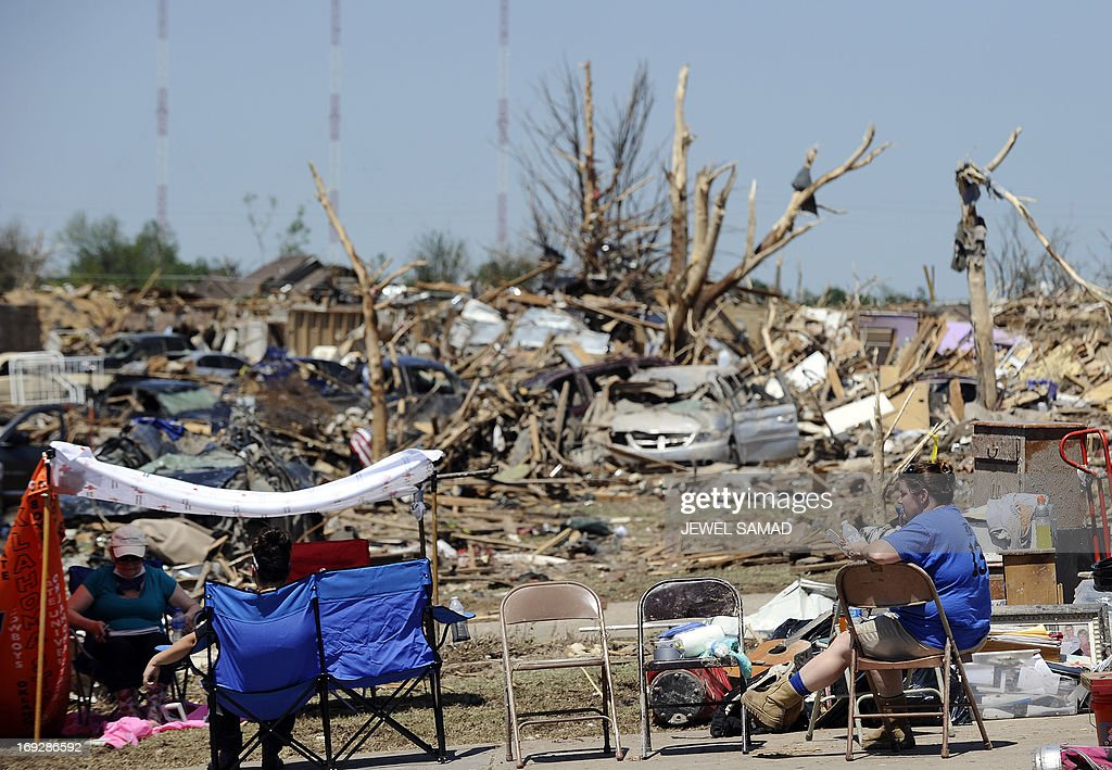 Tornado survivors rest amonst their devasted home on May 22, 2013 in Moore, Oklahoma. As rescue efforts in Oklahoma wound down, residents turned to the daunting task of rebuilding a US heartland community shattered by a vast tornado that killed at least 24 people. The epic twister, two miles (three kilometers) across, flattened block after block of homes as it struck mid-afternoon on May 20, hurling cars through the air, downing power lines and setting off localized fires in a 45-minute rampage. AFP PHOTO/Jewel Samad