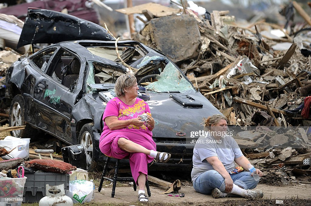 Tornado victims have lunch sitting amongst the rubbles of their home in Moore, Oklahoma, on May 25, 2013. The tornado, one of the most powerful in recent years, killed 24 people, injured 377, damaged or destroyed 1,200 homes and affected an estimated 33,000 people in this Oklahoma City suburb, officials said in their latest update. Initial damages have been estimated at around $2 billion. AFP PHOTO/Jewel Samad