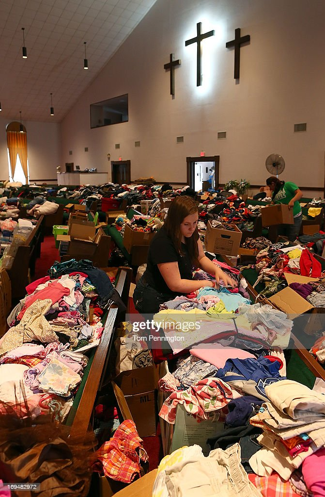 Tornado victims Nicole Ray and Slyler Lusk looks through donated clothing items on May 25, 2013 in Moore, Oklahoma. The tornado of EF5 strength and two miles wide touched down May 20 killing at least 24 people and leaving behind extensive damage to homes and businesses. U.S. President Barack Obama promised federal aid to supplement state and local recovery efforts.