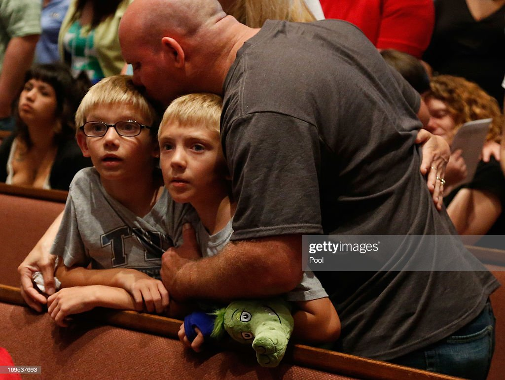 Tornado victims Russell Smith hugs his children and Briarwood Elementary School students, Evan and Justin Smith, during the Oklahoma Strong memorial service held to honor victims of the recent deadly tornado at the First Baptist Church on May 26, 2013 in Moore, Oklahoma. The tornado of EF5 strength and two miles wide touched down May 20 killing at least 24 people and leaving behind extensive damage to homes and businesses. U.S. President Barack Obama visited the area Sunday and promised federal aid to supplement state and local recovery efforts.