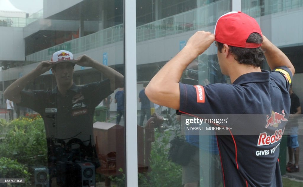 Toro Rosso driver Daniel Ricciardo of Australia looks at his reflection as he adjusts his hat at The Buddh International circuit in Greater Noida on the outskirts of New Delhi on October 24, 2013, ahead of the Formula One Indian Grand Prix 2013. The Formula One Indian Grand Prix 2013 takes place on October 27. AFP PHOTO/Indranil MUKHERJEE