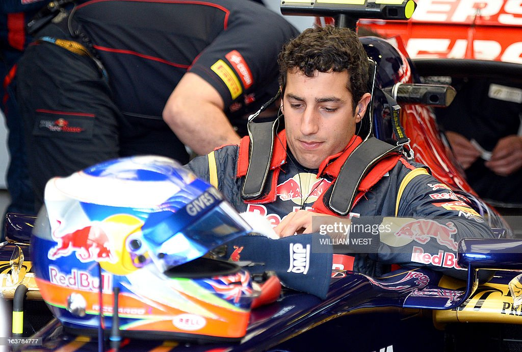 Toro Rosso driver Daniel Ricciardo of Australia lowers himself into his car during the third practice session for the Formula One Australian Grand Prix in Melbourne on March 16, 2013. AFP PHOTO/William WEST IMAGE