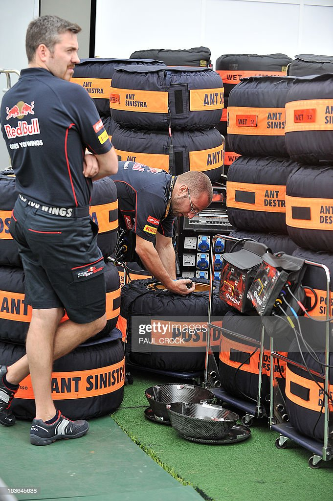 Toro Rosso mechanics check tyres during set-up for the Formula One Australian Grand Prix in Melbourne on March 14, 2013. Reigning World Champion Red Bull Driver Sebastien Vettel of Germany was critical of the new season tyres in pre-season practice. IMAGE RESTRICTED TO EDITORIAL USE - STRICTLY NO COMMERCIAL USE AFP PHOTO / Paul CROCK