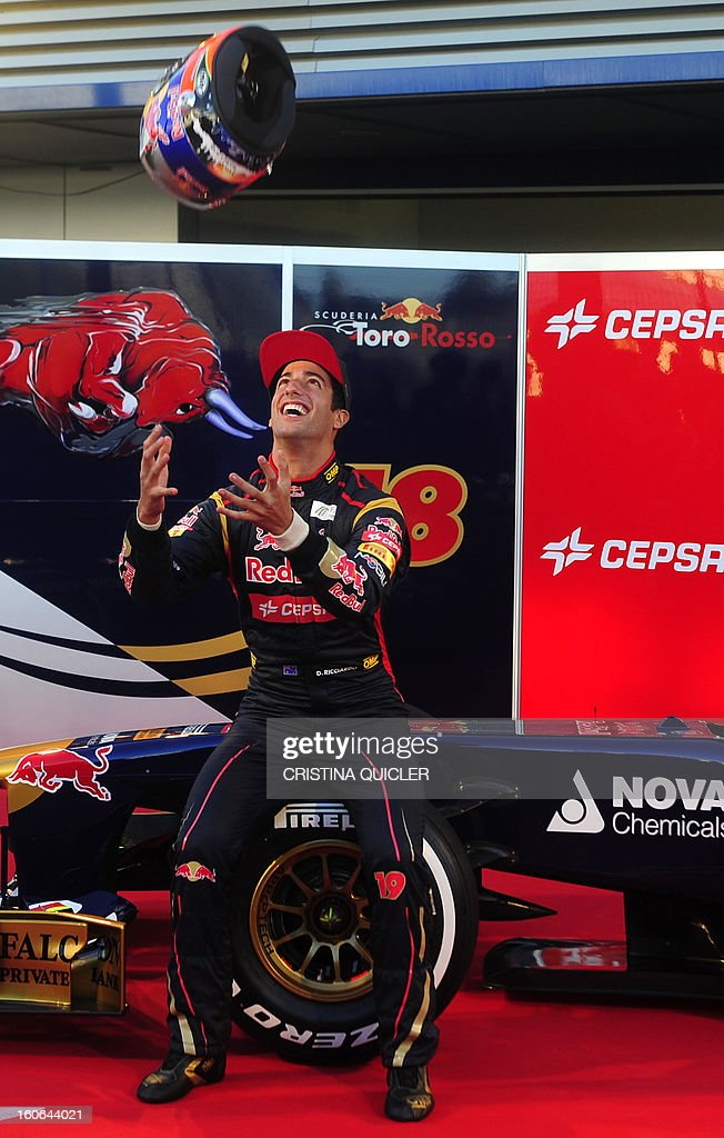 Toro Rosso's Australian driver Daniel Ricciardo throws his helmet in the air as he poses with the new Formula One car STR8 on February 4, 2013 as part of a training session at the Jerez de la Frontera racetrack. AFP PHOTO/ CRISTINA QUICLER