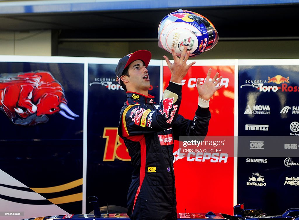 Toro Rosso's Australian driver Daniel Ricciardo throws his helmet in the air as he poses with the new Formula One car STR8 on February 4, 2013 as part of a training session at the Jerez de la Frontera racetrack.