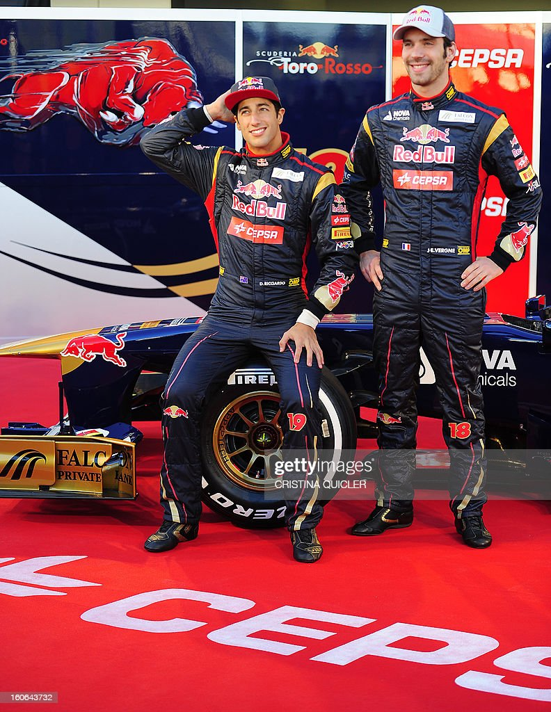Toro Rosso's drivers, Australian Daniel Ricciardo (L) and French Jean-Eric Vergne pose with the new Formula One car STR8 on February 4, 2013 as part of a training session at the Jerez de la Frontera racetrack.