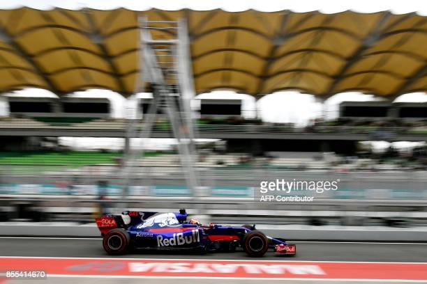 Toro Rosso's French driver Pierre Gasly drives in pit lane during the second practice session of the Formula One Malaysia Grand Prix in Sepang on...