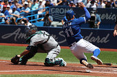 TORONTO ON JULY 23 Toronto Blue Jays center fielder Kevin Pillar slides into home safely behind Seattle Mariners catcher Chris Iannetta for the first...