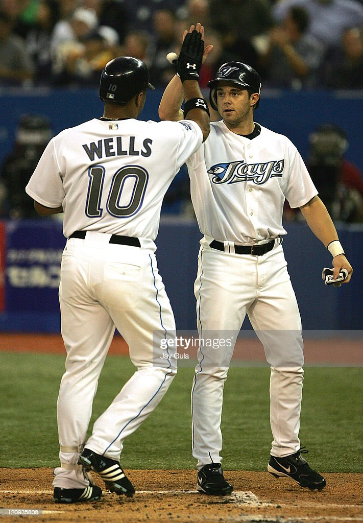 Toronto Blue Jays CF Vernon Wells is congratulated by OF Frank Catalanotto after hitting a 2 run HR in the 1st inning in action at Rogers Centre in...