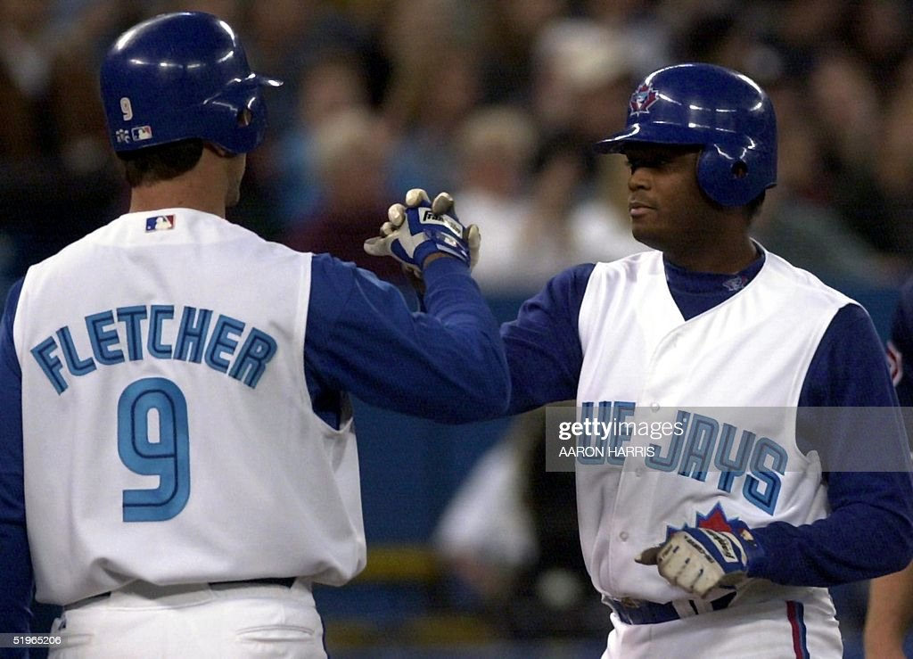 Toronto Blue Jays' Darrin Fletcher (L) congratulates teammate Tony Batista (R) as he comes in on a two-run homer during the first inning against the New York Yankees 22 April 2000 in Toronto, Canada. The Jays went on to beat the Yankees 8-2.