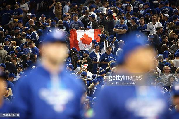 Toronto Blue Jays fans hold up a Canadian flag after game three of the American League Championship Series between the Toronto Blue Jays and the...