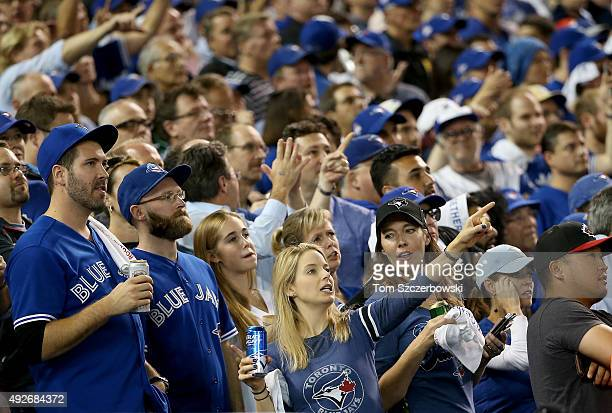Toronto Blue Jays fans look up at the scoreboard in the seventh inning while taking on the Texas Rangers in game five of the American League Division...