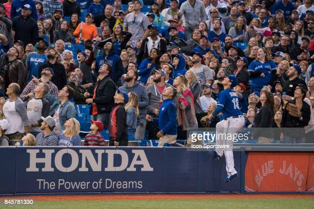 Toronto Blue Jays Infielder Darwin Barney climbs the fence get a better look at a foul ball hit during the regular season MLB game between the...