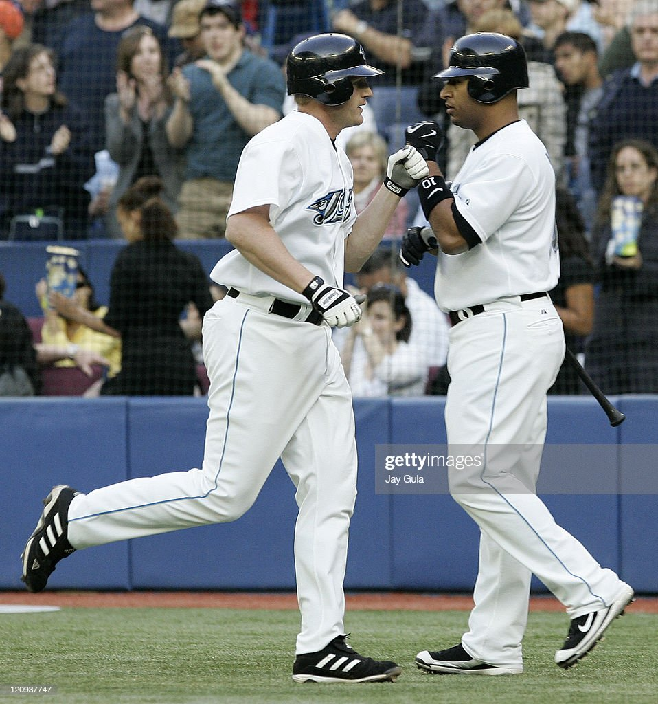 Toronto Blue Jays Lyle Overbay is congratulated by Vernon Wells after hitting his 8th HR of the season vs the New York Yankees at Rogers Centre in...