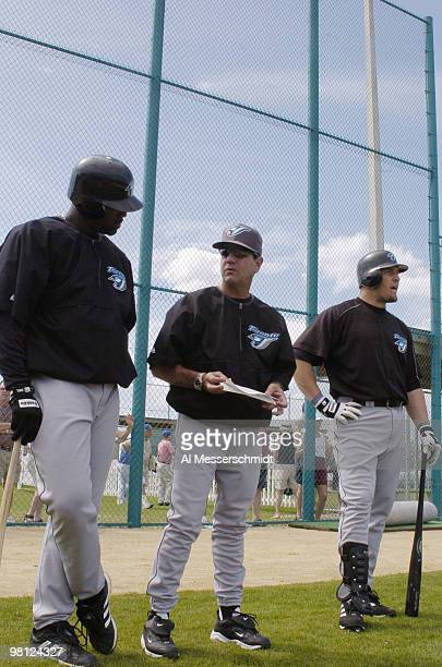 Toronto Blue Jays manager Carlos Tosca watches batting drills with sluggers Carlos Delgado and Eric Hinske during practice March 3 2004 in Dunedin...
