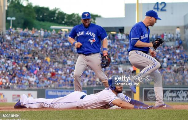 Toronto Blue Jays pitcher JA Happ right takes the toss from first baseman Kendrys Morales to touch first before the Kansas City Royals' Eric Hosmer...