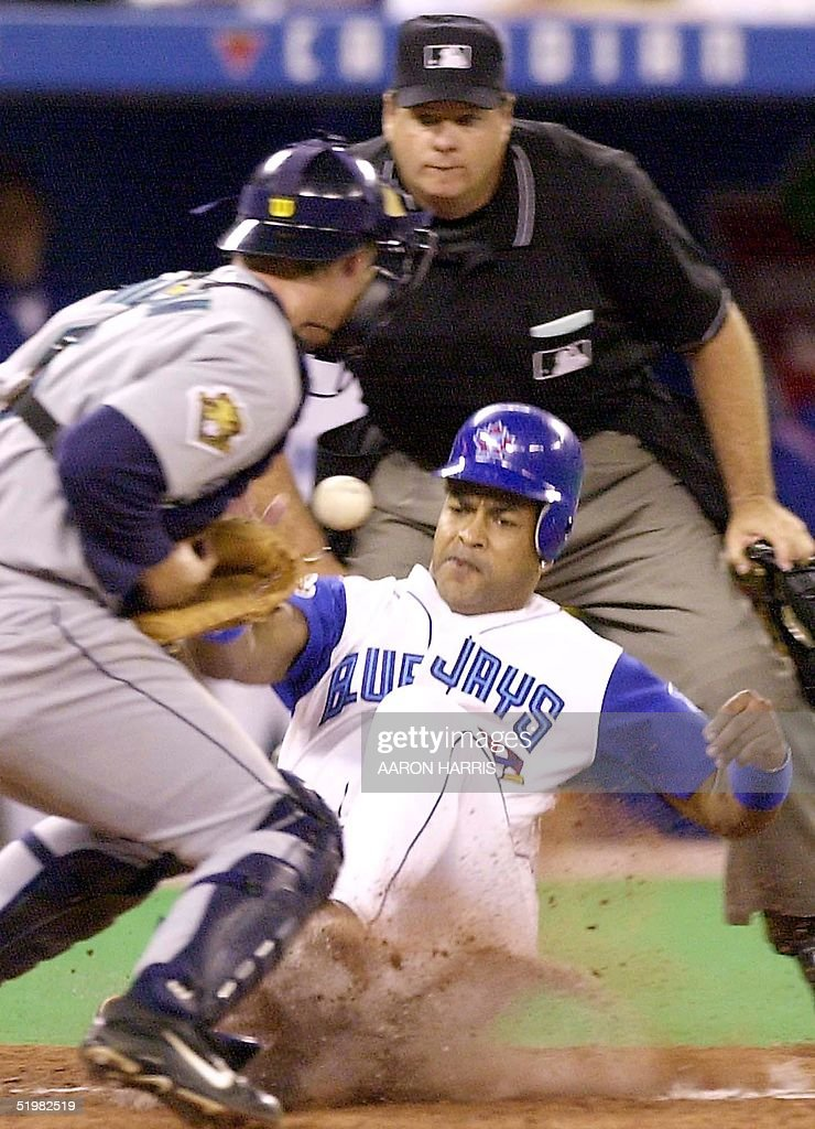 Toronto Blue Jays' Raul Mondesi (R) slides safely into home in front of Seattle Mariners' catcher Dan Wilson during fifth inning action in Toronto, Canada, 12 May, 2001. The Mariners beat the Jays 11-7.
