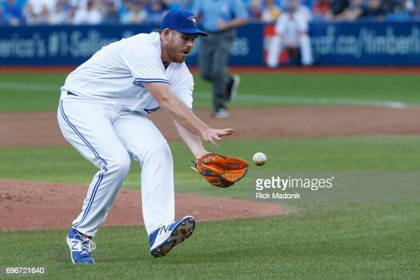Toronto Blue Jays relief pitcher Joe Biagini fields a ball but then has a throwing error when he tosses the ball over Justin Smoak Toronto Blue Jays...