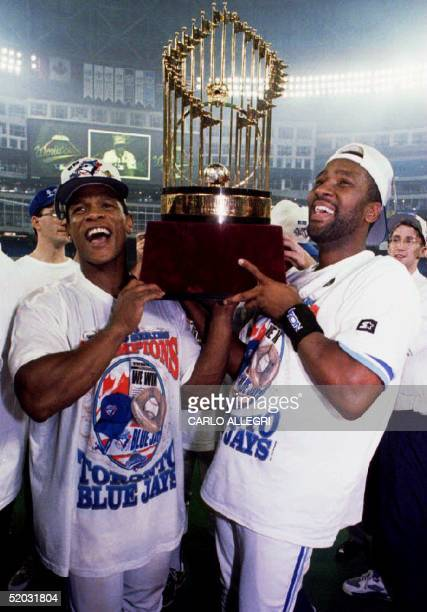 Toronto Blue Jays Rickey Henderson and Joe Carter lift the World Series trophy for Blue Jays fans late 23 October 1993 in Ontario Canada after the...