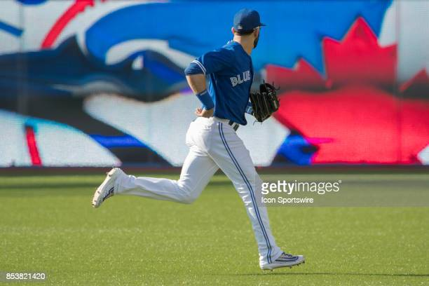 Toronto Blue Jays Right fielder Jose Bautista takes the field in the first inning and takes a long look at the team logo to start the game during the...