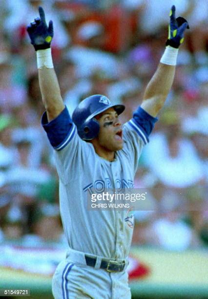 Toronto Blue Jays Roberto Alomar raises his arms as he watches the ball he just hit off of Oakland A's Dennis Eckersley sail over the right field...