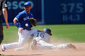 Toronto Blue Jays second baseman Devon Travis handles the throw but its late as San Diego Padres center fielder Travis Jankowski slides safely into...