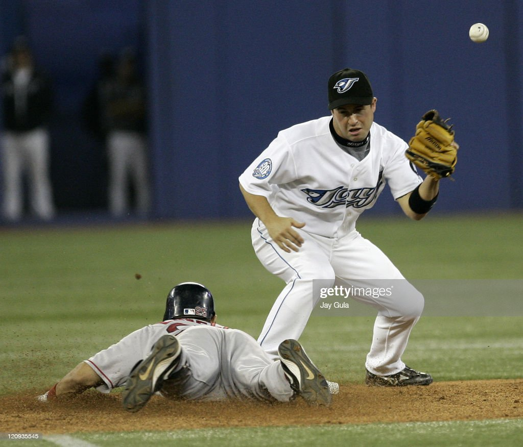 Toronto Blue Jays SS John McDonald bobbles the relay from the outfield to allow Boston's Mike Lowell to slide safely into second with a double at...