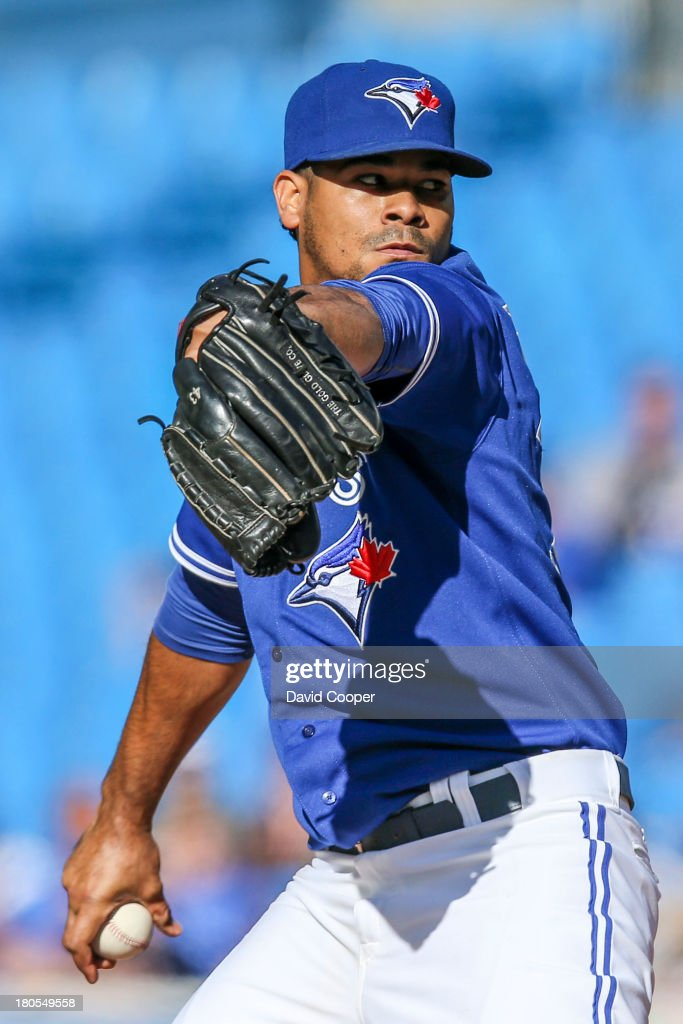TORONTO ON - Toronto Blue Jays starting pitcher Esmil Rogers (32) continues to use a borrowed glove from R.A. Dickey (See the (43) on the glove's index finger) during the game between the Baltimore Orioles and the Toronto Blue Jays September 14, 2013.