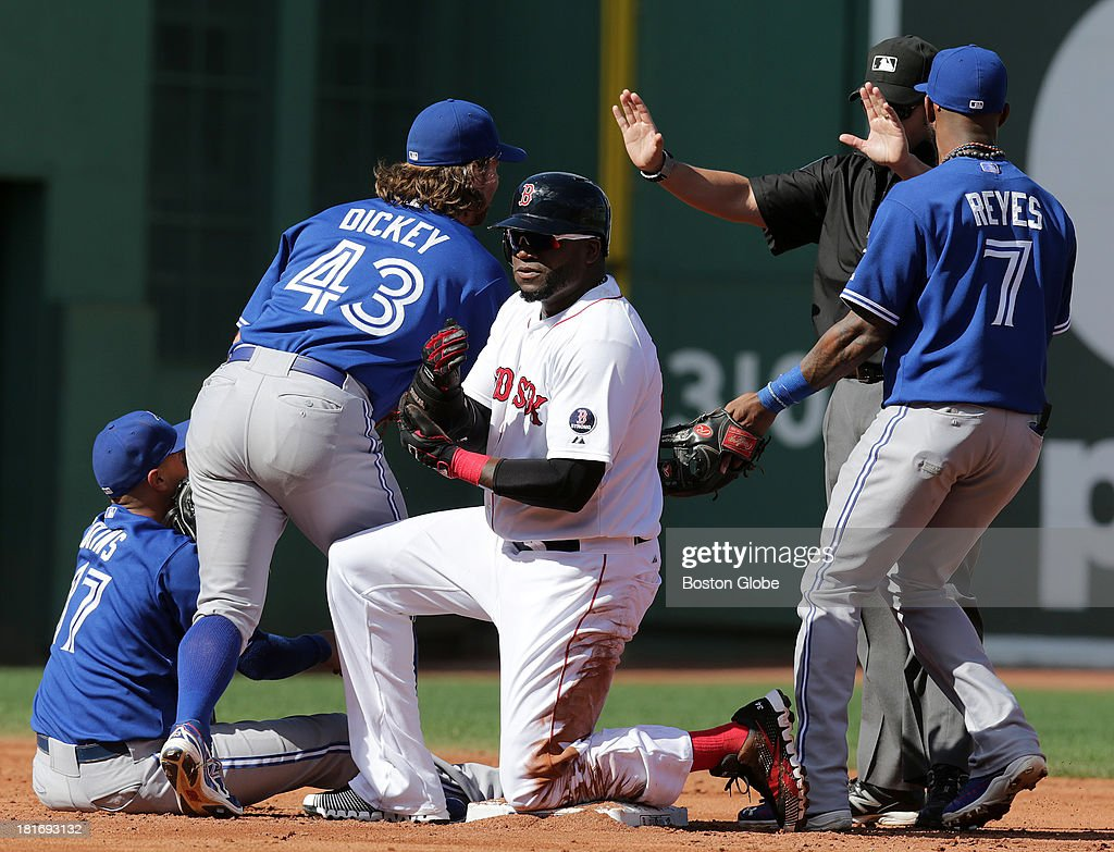 Toronto Blue Jays starting pitcher R.A. Dickey (#43) second baseman Ryan Goins (#17) and shortstop Jose Reyes (#7) argued the call with umpire Manny Gonzalez (#79) in the third inning. The Boston Red Sox host the Toronto Blue Jays in game three of a three-game series at Fenway Park.