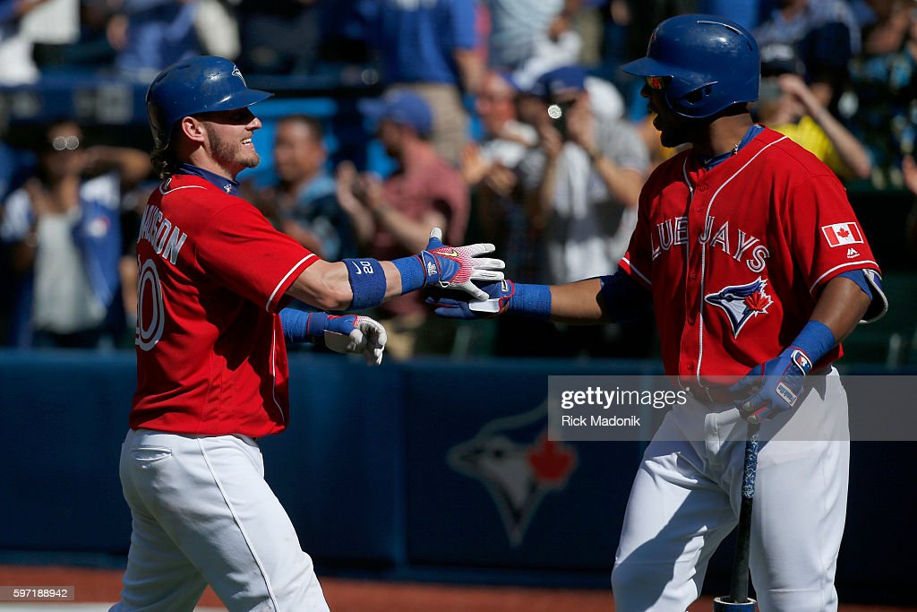 Toronto Blue Jays third baseman Josh Donaldson is greeted at home by Toronto Blue Jays designated hitter Edwin Encarnacion after hitting his 3rd home...