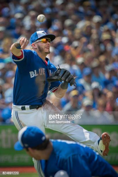 Toronto Blue Jays Third baseman Josh Donaldson leaps to make a quick throw to first as the pitcher ducks during the regular season MLB game between...