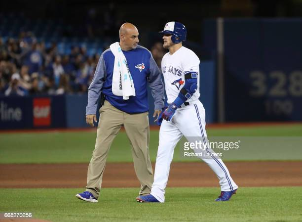 TORONTO ON APRIL 13 Toronto Blue Jays third baseman Josh Donaldson walks off the field with a trainer after legging out a double in the 6th and...
