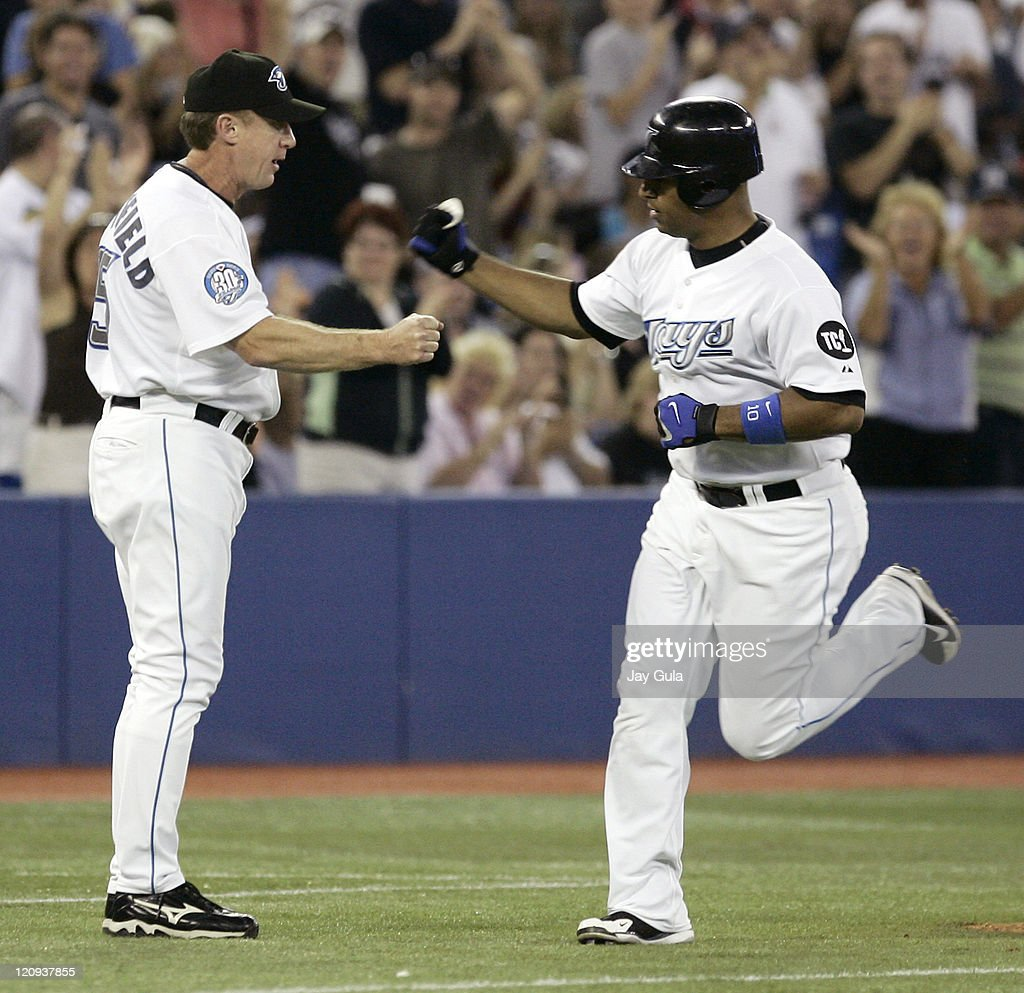 Toronto Blue Jays Vernon Wells gets congratulations from 3rd base coach Brian Butterfield after slugging his 29th home run of the season vs the...
