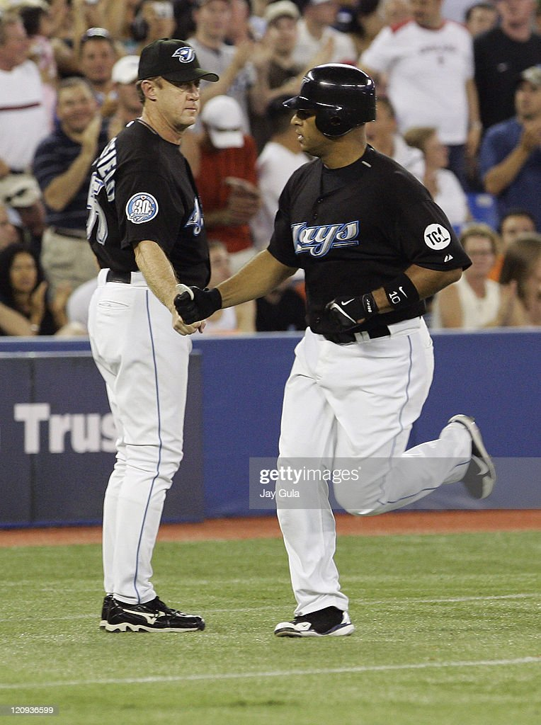 Toronto Blue Jays Vernon Wells is congratulated by 3rd base coach Brian Butterfield after Wells blasted his 26th HR of the season against the New...