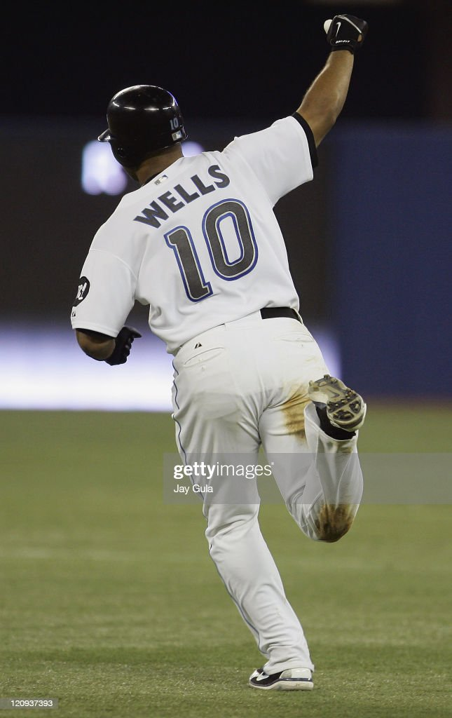 Toronto Blue Jays Vernon Wells pumps his fist in the air after the ball he hit cleared the left field fence for a game winning HR his 24th of the...