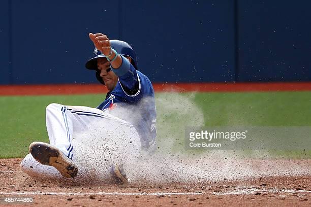Toronto Canada August 29 Toronto Blue Jays second baseman Ryan Goins slides home off an Encarnacion homer during MLB action against the Detroit...