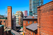 Photo of old brick towers of the chic Distillery District with new condos and downtown skyscrapers in the background in Toronto, Ontario, Canada.