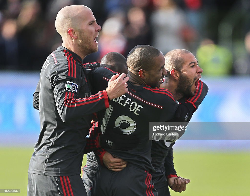 Toronto, Canada - March 22 - In second half action, star striker Jermain Defoe celebrates after scoring the only goal of the game with team mates, <a gi-track='captionPersonalityLinkClicked' href=/galleries/search?phrase=Michael+Bradley+-+Soccer+Player&family=editorial&specificpeople=7022299 ng-click='$event.stopPropagation()'>Michael Bradley</a> (left) and Jonathan Osorio The Toronto Football Club took beat the DC United 1-0 in their home opener at BMO field. The game marks a new chapter with some superstar players. March 22, 2014