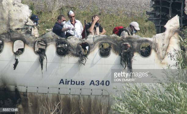 Officials view he wreckage of the Air France Airbus A340 at Toronto's Pearson International Airport 03 August 2005 one day after it skid off the...