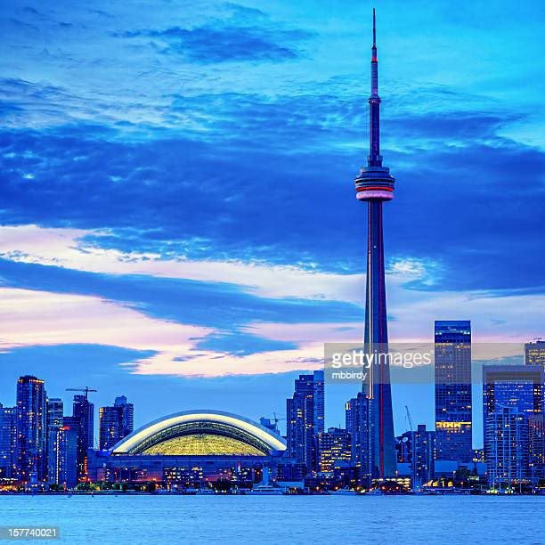 Toronto cityscape with CN Tower and baseball stadium at dusk