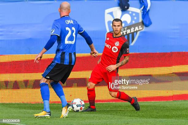Toronto FC forward Sebastian Giovinco looks to pass the ball in front of Montreal Impact defender Laurent Ciman during the Toronto FC versus the...
