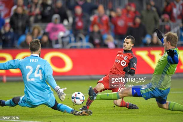 Toronto FC Forward Sebastian Giovinco trys to split Seattle Sounders Goalkeeper Stefan Frei and teammate defender Chad Marshall to shoot on goal...