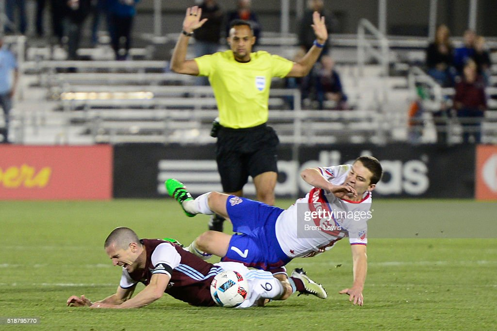Toronto FC forward Will Johnson falls over the back of Colorado Rapids midfielder Sam Cronin during the second half at Dick's Sporting Goods Park on...
