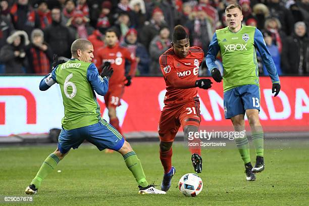 Toronto FC Mid Fielder Armando Cooper controls the ball in front of Seattle Sounders Defender Osvaldo Alonso during the MLS Cup final game between...