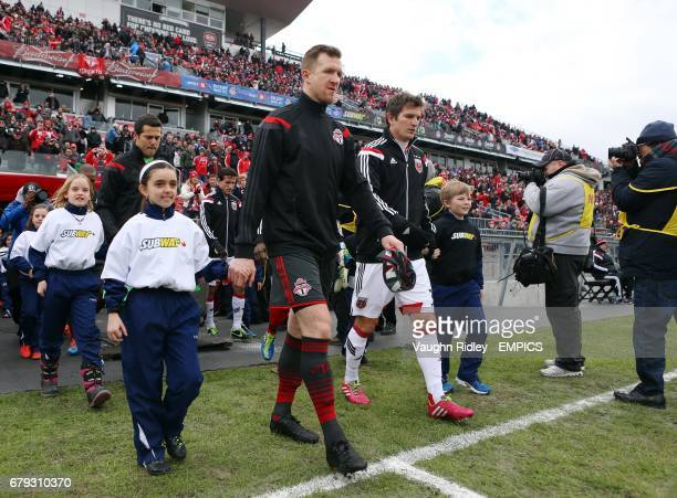 Toronto FC's Captain Steven Caldwell and DC United's Captain Bobby Boswell lead their teams out of the tunnel