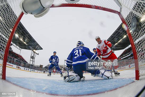 Toronto Maple Leafs alumni Cutis Joseph makes a save against Detroit Red Wings alumni Darren McCarty as Toronto Maple Leafs alumni Borje Salming...